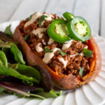 Sloppy joe baked potato with chipotle sauce, jalapenos, and salad on a white plate.