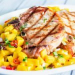 Pork chop with grill marks on top of white plate with mango salsa.